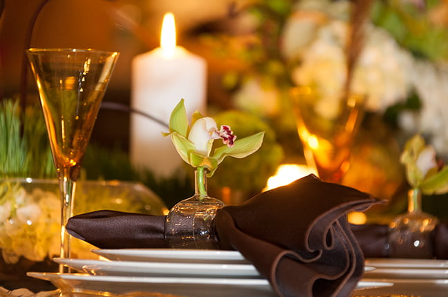 Vela, taça, flores e itens complementares para mesa