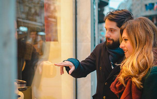 casal vendo vitrine de loja